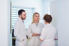 小组资深医生和年轻人护理患者审查的医疗报告  的医生队  库存照片
