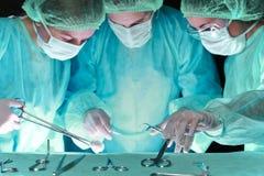 小组进行操作的面具的外科医生 以绿色上色的手术室场面 医学,手术和 免版税库存照片