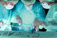 小组进行操作的面具的外科医生 以绿色上色的手术室场面 医学,手术和 免版税库存图片