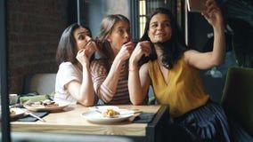 小组采取在咖啡馆藏品智能手机的朋友女孩selfie坐在桌上 股票视频