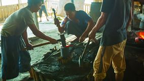 小组铁匠工作在铁匠铺 库存图片