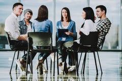 小组青年人坐在圈子的椅子 免版税库存照片