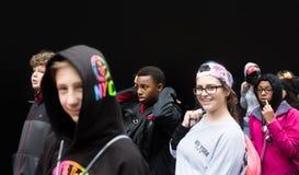 小组青年人对黑墙壁 库存图片