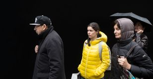 小组青年人对黑墙壁 免版税图库摄影