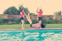 小组3个少年女朋友获得乐趣在游泳池 猛撞的戏剧在水池 库存图片
