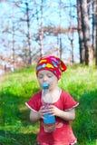 小美丽的女孩与弄糟拿着瓶的你的眼睛 库存照片