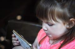 小美丽的女孩享用电话 开玩笑技术 库存图片