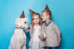 小美丽的女孩和英俊的男孩有狗的庆祝生日 友谊 家庭 在蓝色背景的演播室画象 免版税库存图片