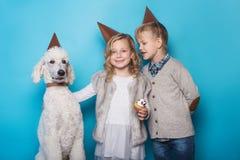 小美丽的女孩和英俊的男孩有狗的庆祝生日 友谊 家庭 在蓝色背景的演播室画象 库存照片