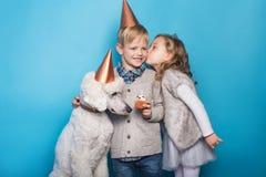 小美丽的女孩和英俊的男孩有狗的庆祝生日 友谊 家庭 在蓝色背景的演播室画象 免版税库存照片