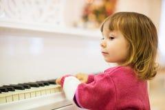 小美丽的女孩在一架白色大平台钢琴使用 库存照片