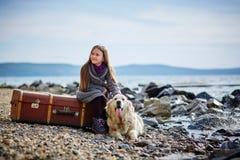 小美丽的女孩在与狗,猎犬的海滩走 免版税库存图片