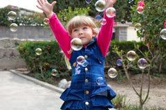 小美丽的女孩在他们的手上走与一个软的玩具 在露天 使用与肥皂泡的小女孩在庭院里 免版税库存照片