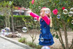 小美丽的女孩在他们的手上走与一个软的玩具 在露天 使用与肥皂泡的小女孩在庭院里 免版税库存图片