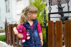 小美丽的女孩在他们的手上走与一个软的玩具 在露天 免版税库存照片