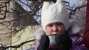 小美丽的女孩在冬天喝在街道的茶 股票视频