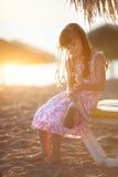 小美丽的女孩坐海滩在日落 免版税图库摄影