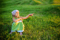 小美丽的女孩坐草 库存图片
