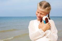 小美丽的女孩拥抱一条可笑的狗-玩具 喜爱的软的玩具 免版税图库摄影