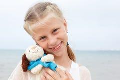 小美丽的女孩拥抱一条可笑的狗-玩具 喜爱的软的玩具 库存图片