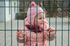 小美丽的女孩婴孩哭泣与在他的眼睛的泪花的和作为对金属la篱芭的一项处罚被关闭的哀伤,哀伤的情感  库存照片