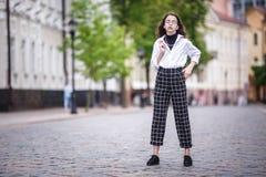 小美丽的时髦的孩子女孩画象有太阳镜和短的方格花纹裤的在城市都市街道 免版税库存照片