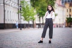 小美丽的时髦的孩子女孩画象有太阳镜和短的方格花纹裤的在城市都市街道 免版税图库摄影