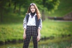 小美丽的时髦的孩子女孩画象有太阳镜和短的方格花纹裤的在绿色森林背景的城市公园 图库摄影
