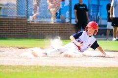 小职业棒球联盟下滑的棒球运动员在家。 库存照片