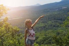 小聪慧的女孩坐在山边缘并且调查在山的距离 免版税库存图片