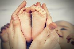 小脚婴孩拿着他的她的手的母亲 免版税库存图片