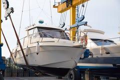 小船举起汽艇的轮式起重机逐年绘 免版税库存照片