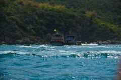 小船乘驾和船在海岛绿色山海洋海背景中 免版税库存图片