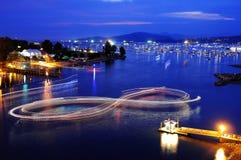 小船事假一个8字符的光足迹队在海水的在蓝色小时,在烟花竞争前开始了 库存照片