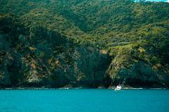 小船前绿色海岛 免版税库存图片