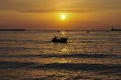 小船剪影在日落背景的 库存照片