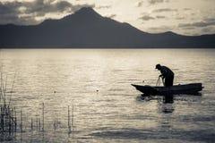 小船剪影的湖渔夫 库存照片