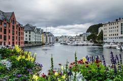 小船和大厦看法在有五颜六色的花的Alesund市中心小游艇船坞在前景 图库摄影