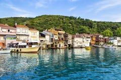 小船和房子在阿纳多卢Kavagi村庄海边 免版税库存照片