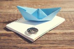 小船和指南针在笔记薄在木背景 免版税库存图片