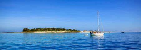 小船和有白色海滩的美丽的斐济环礁海岛 图库摄影