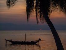 小船和棕榈树的剪影反对落日的与云彩 免版税库存图片