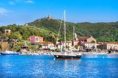小船和海滩旅馆在有一台风车的科利乌尔村庄在小山顶部,鲁西永, V 免版税库存照片