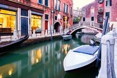 小船和老房子一条狭窄的运河的在威尼斯日落的 库存图片