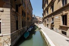 小船和长平底船典型的看法在微小的桥梁下在威尼斯运河  免版税图库摄影