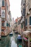 小船在一条狭窄的威尼斯式运河的破旧的大厦附近停放了 图库摄影