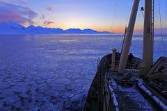 小船在冬天北极 白色多雪的山,蓝色冰川斯瓦尔巴特群岛,挪威 冰在海洋 在北极的冰山微明 桃红色克洛 库存图片