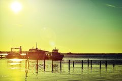 小船在小船驻地的码头在黎明太阳的光芒 免版税库存图片