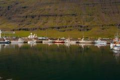 小船在山风景的海靠了码头在Sejdisfjordur,冰岛 在旅行由水的沿海的水上艺术 免版税库存图片