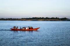 小船在有游人和商人的河 免版税库存照片
